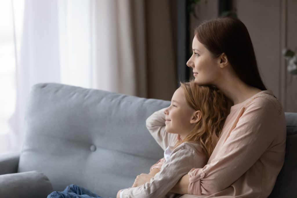 Caring young mom and little daughter dream at home